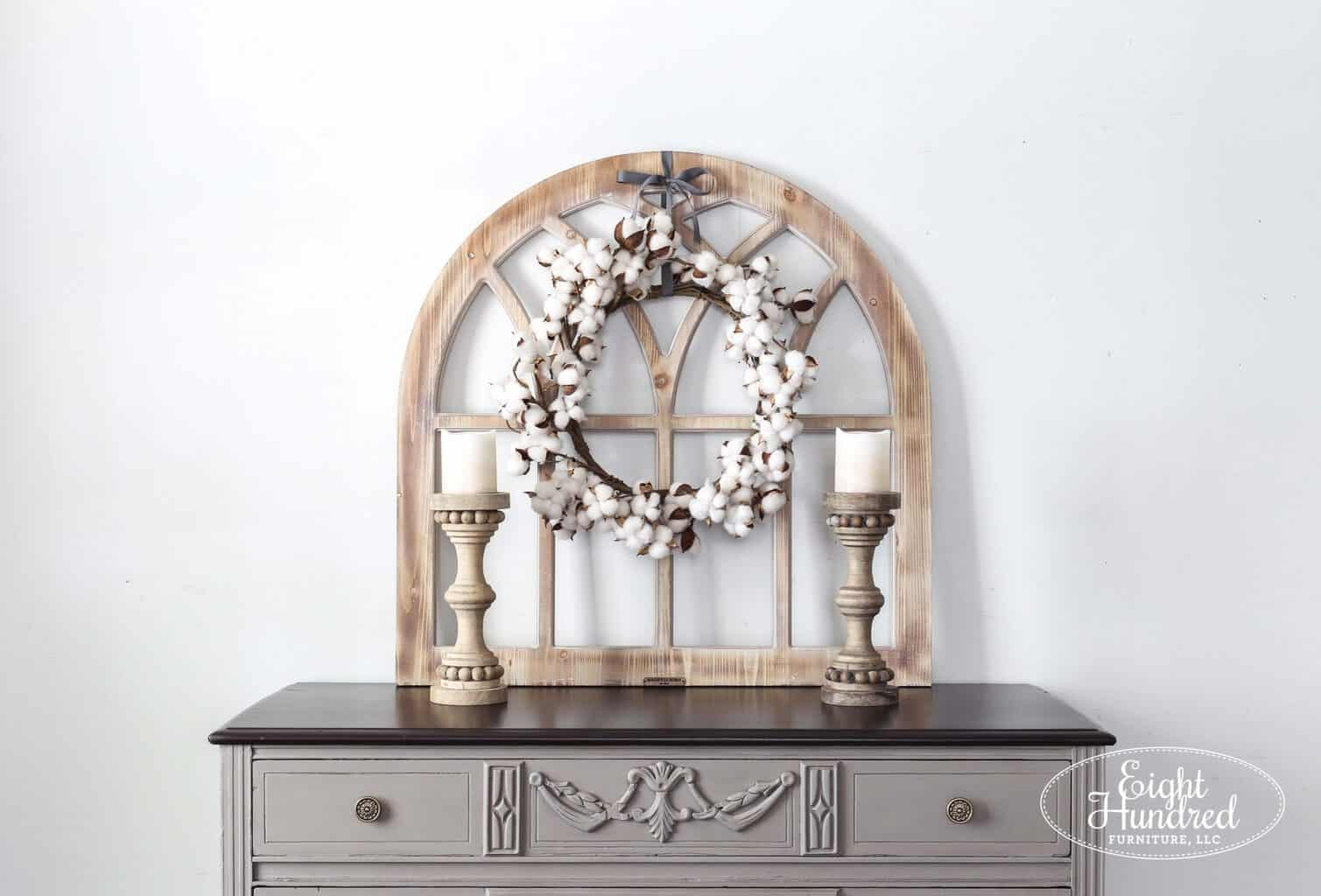 Wooden arch with cotton wreath and wooden candlesticks on French Linen dresser