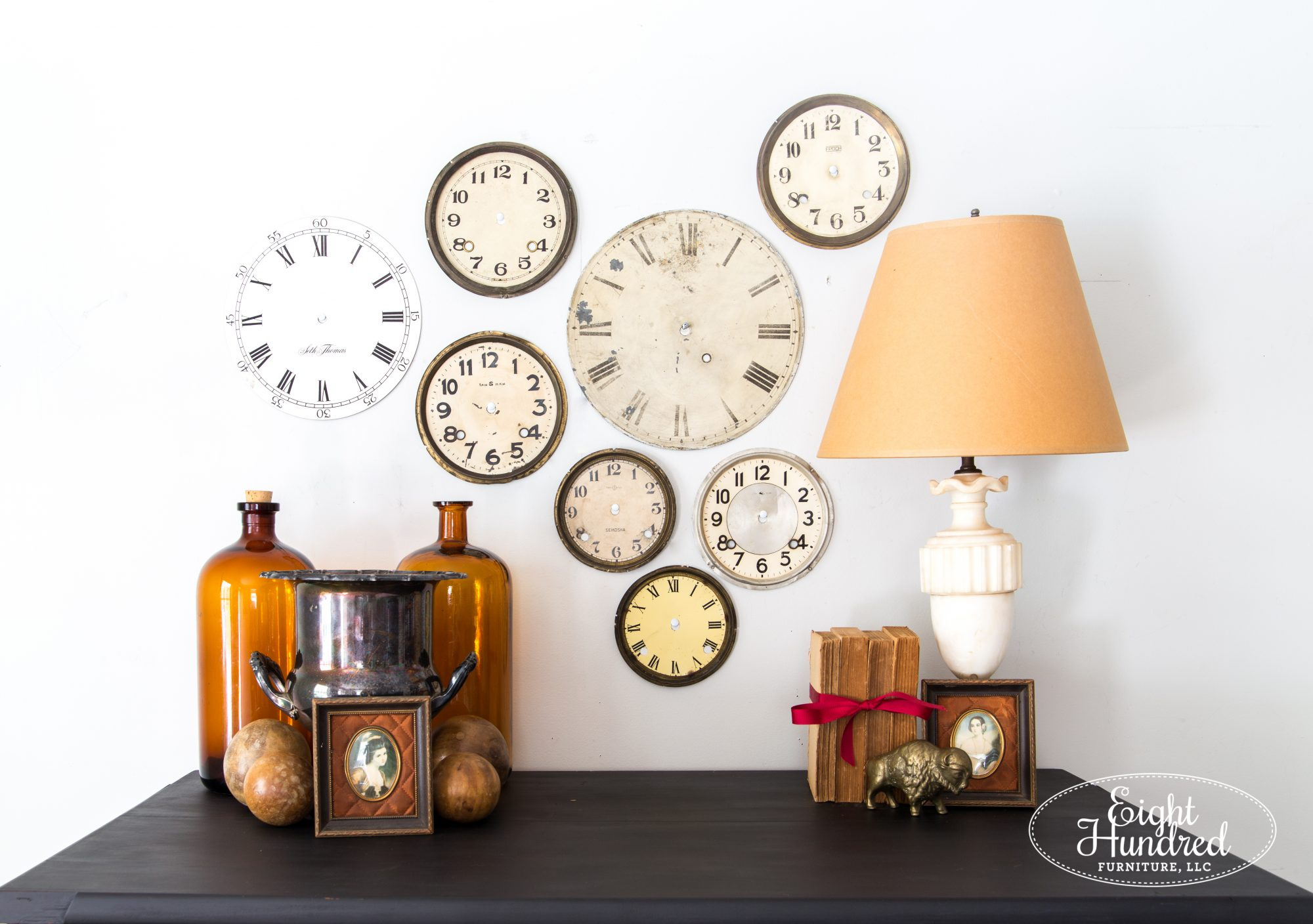 Collage of clock faces, amber bottles, alabaster lamp, wooden balls, silver ice bucket
