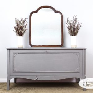 Vintage cedar chest painted in General Finishes Perfect Gray Milk Paint with a mirror on top and two faux floral arrangements on top