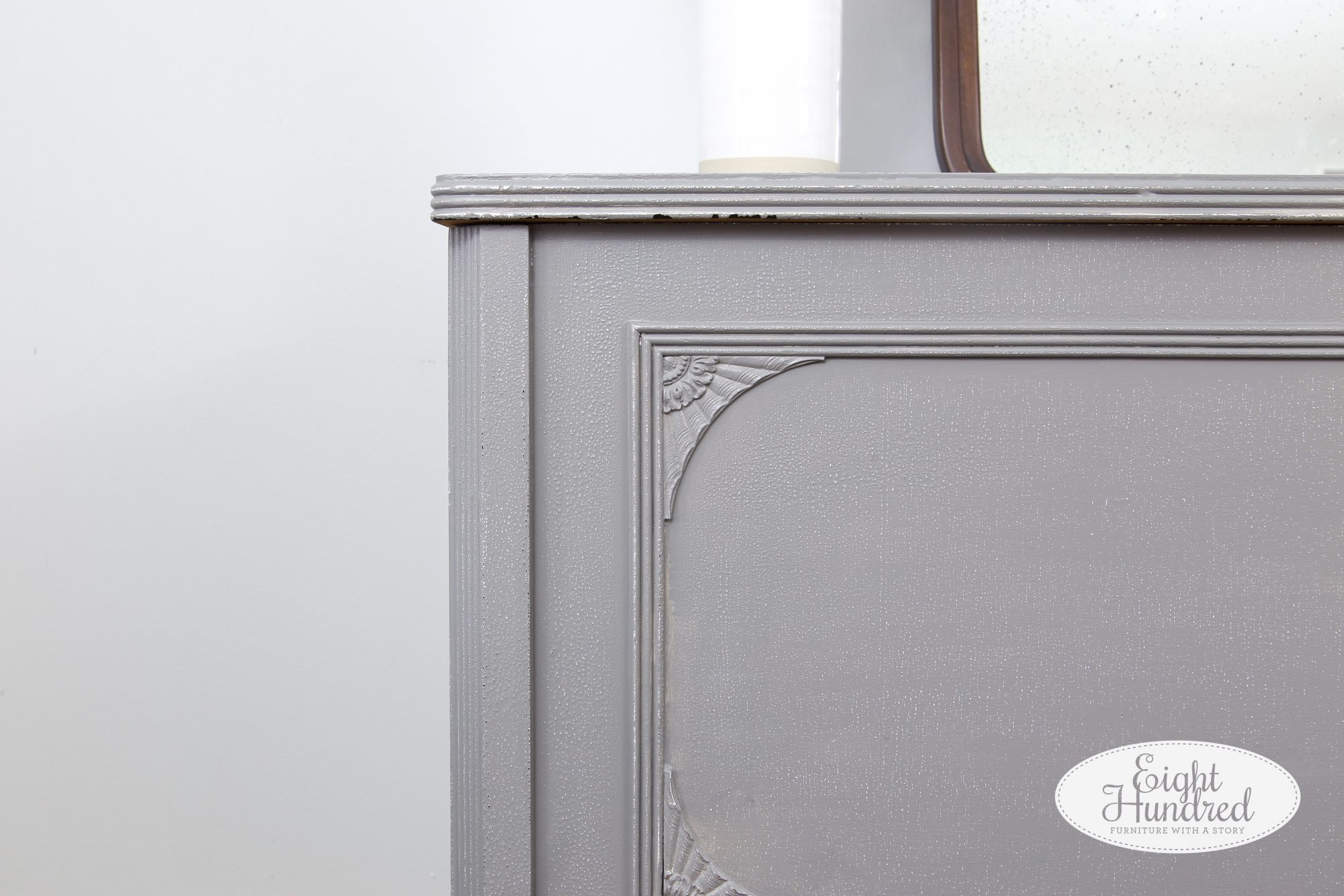 Corner of vintage cedar chest showing distressed edges painted in General Finishes Perfect Gray Milk Paint