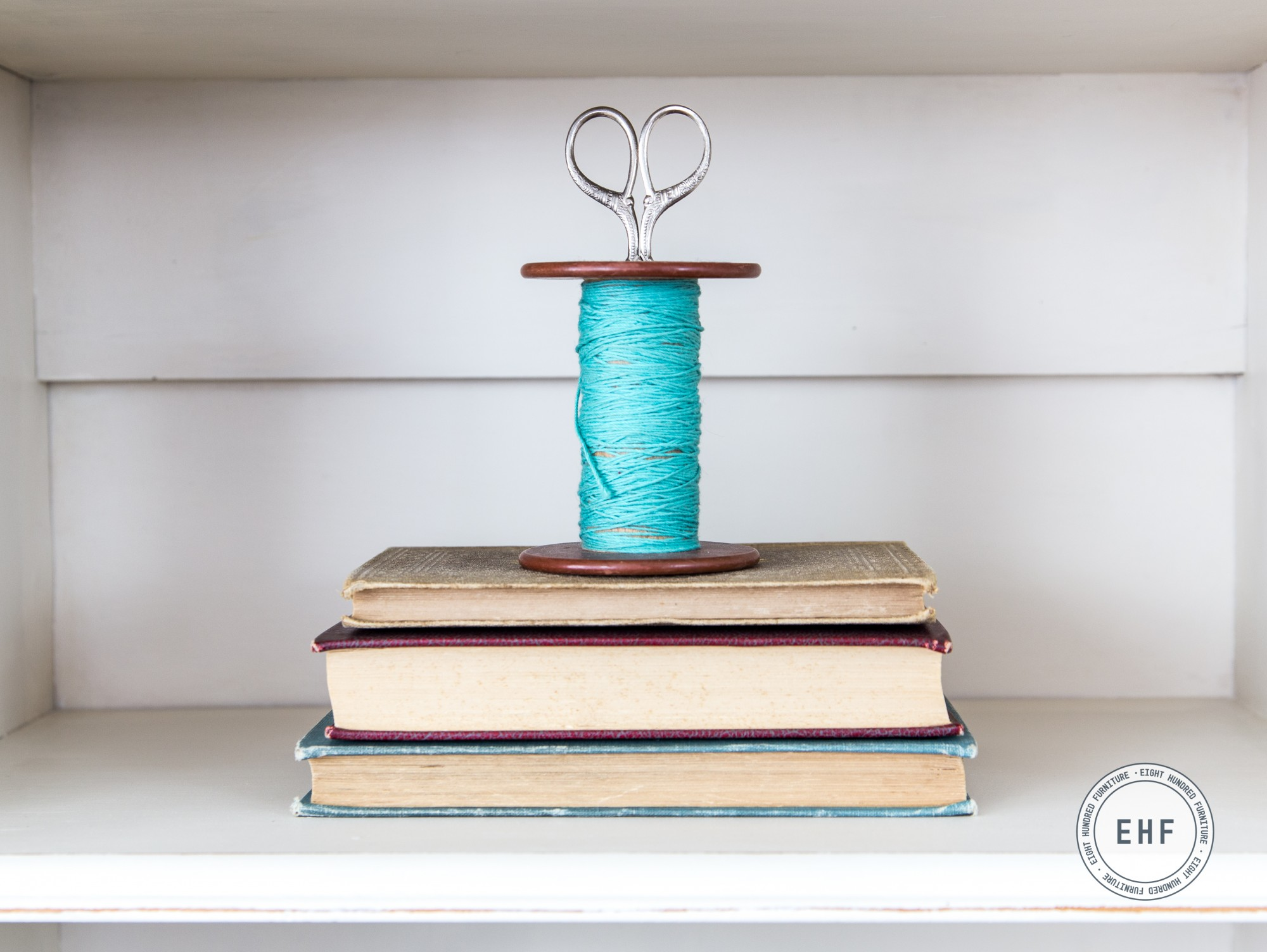 Spool of teal thread on a stack of books