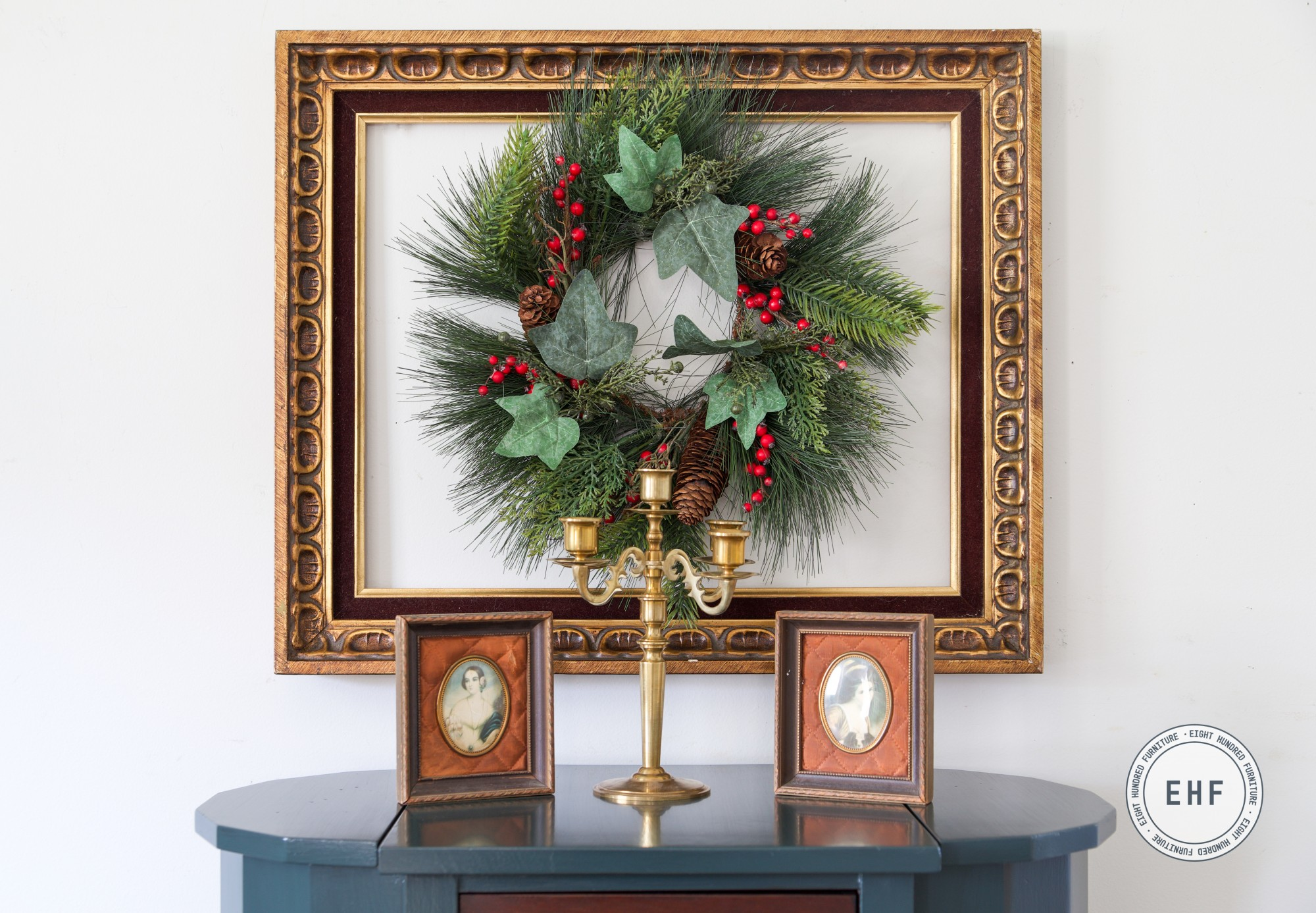 Christmas wreath in gold frame with brass candelabra