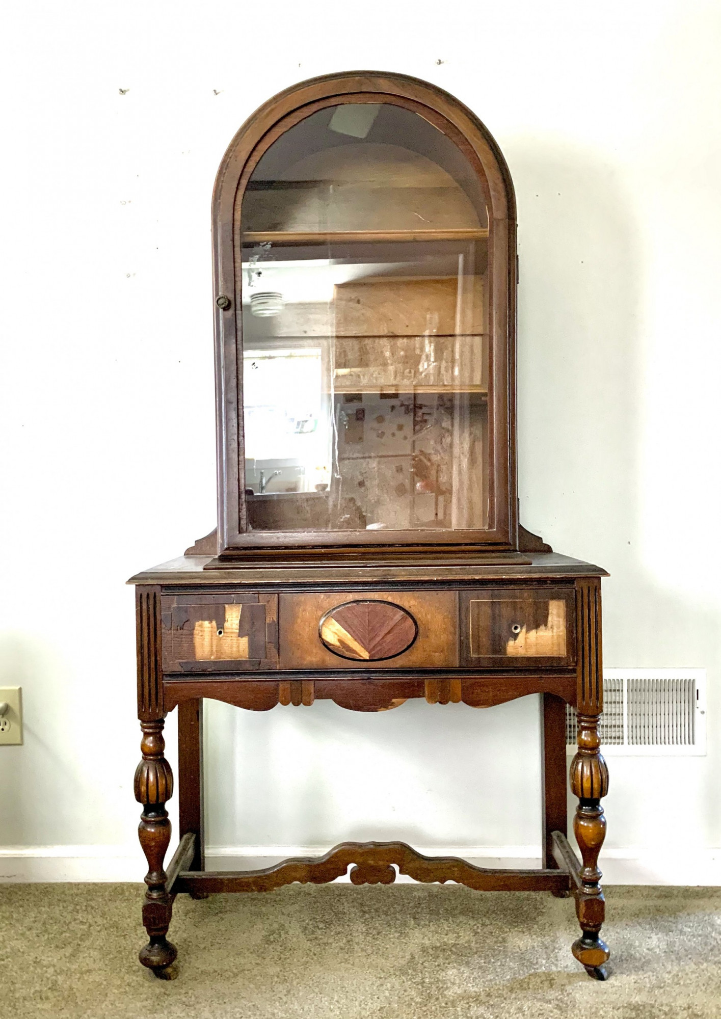 Vintage china cabinet with damaged veneer