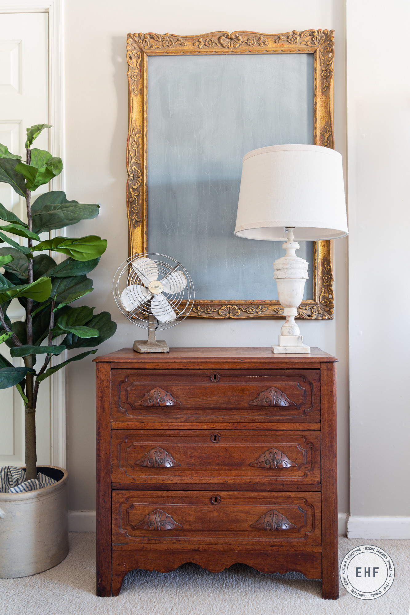 Antique victorian chest of drawers with alabaster lamp, vintage fan, fiddle leaf fig tree and wall chalkboard in Aviary by Miss Mustard Seed's Milk Paint
